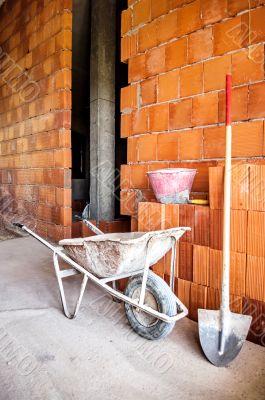masonry, wheelbarrow, bricks and shovel