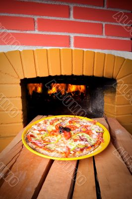 Pizza baking with wood fire in the oven