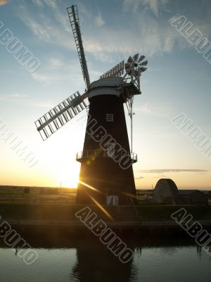 Sun setting behind windmill