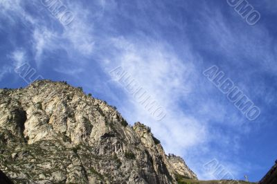 Bright blue sky and clouds above a mountain