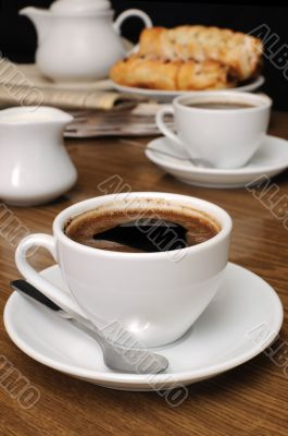 cup of fragrant black coffee on the table with milk and a bun
