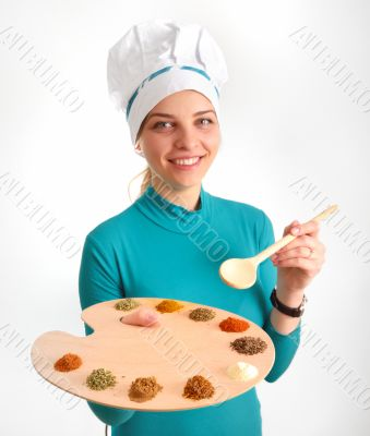 Spices and herbs on the palette and cook girl