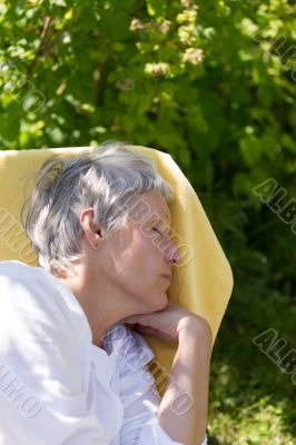 Aged woman sleeping on lounger