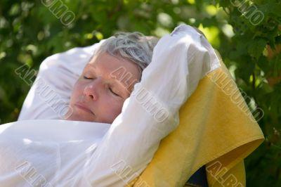Senior woman sleeping on lounger