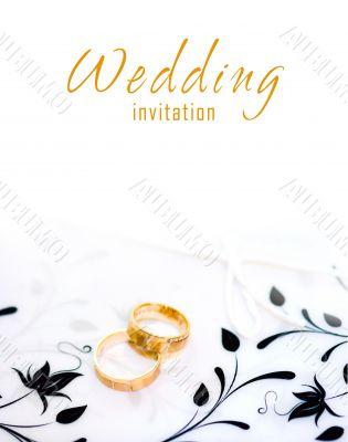 Golden rings on a wedding invitation