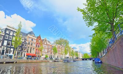 Traditional Houses and house boat along canal in Amsterdam