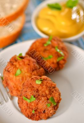 meat balls with mustard on white dish