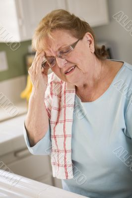 Senior Adult Woman At Kitchen Sink With Head Ache