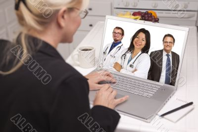 Woman In Kitchen Using Laptop, Online with Nurses or Doctors
