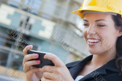 Female Contractor Wearing Hard Hat on Site Texting with Phone
