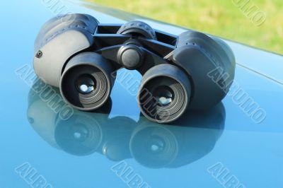 Binoculars lying on the car hood.