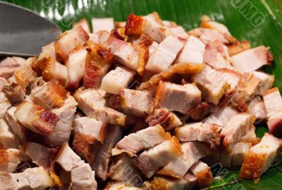 Roast pork cut into pieces on palm leaf