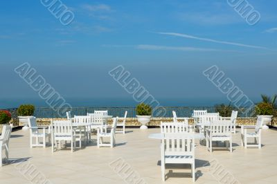 An empty rooftop restaurant with views of the sea