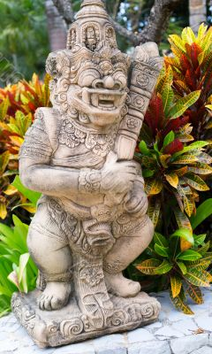 Thai stone god in the bushes of tropical plants