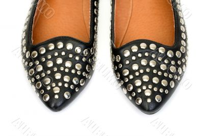 Black women`s leather ballet flats with steel rivets close up