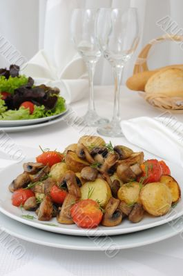 Baked potatoes with slices of mushrooms and tomatoes