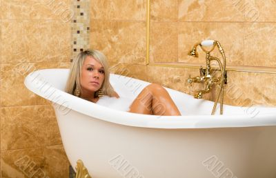 Tanned girl is lying in the bath