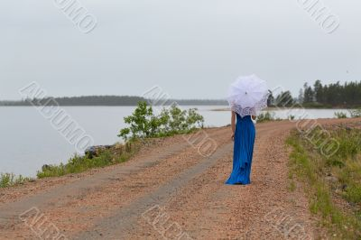 Slim girl in a dress with an umbrella in a forest