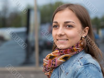 portrait of a beautiful girl in a denim jacket with a scarf