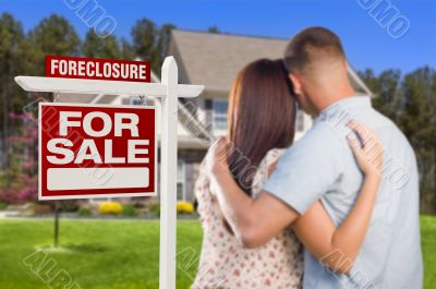 Military Couple Standing in Front of Foreclosure Sign and House
