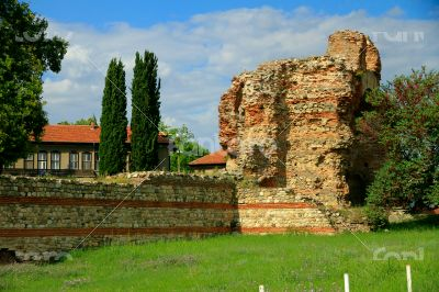 Ancient ruins on the background of modern buildings in the city