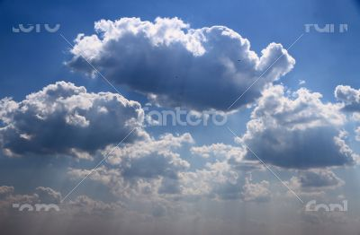 Bright blue sky with puffy white clouds.