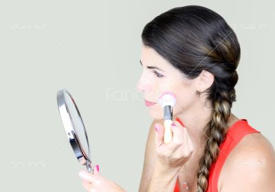 Attractive young woman looking at the mirror, applying make up