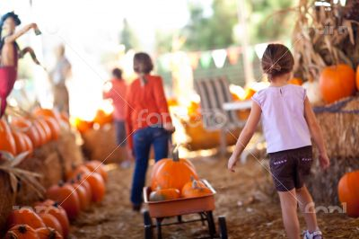 Two Little Girls Pulling Their Pumpkins In A Wagon