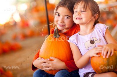 Little Girls Holding Their Pumpkins At A Pumpkin Patch