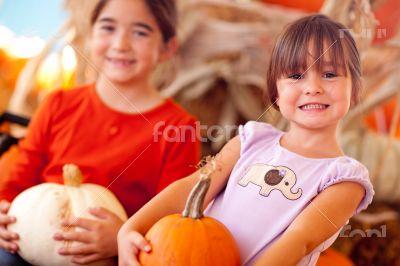 Two Cute Little Girls Holding Their Pumpkins At A Pumpkin Patch