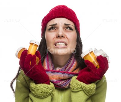 Sick Mixed Race Woman with Empty Medicine Bottles Blowing Nose