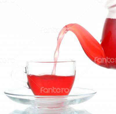 Tea being poured into glass tea cup isolated