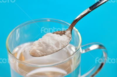 Spoon of baking soda over glass of water