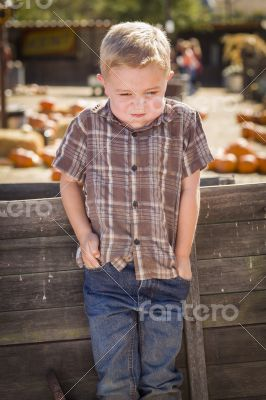 Frustrated Boy at Pumpkin Patch Farm Standing Against Wood Wagon