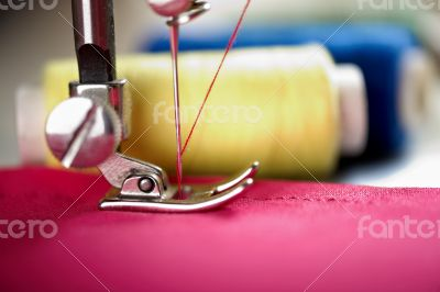 Close up of threads on fabric and sewing machine.