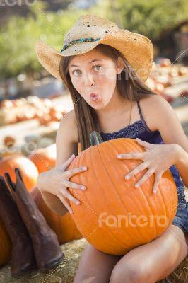 Preteen Girl Holding A Large Pumpkin at the Pumpkin Patch