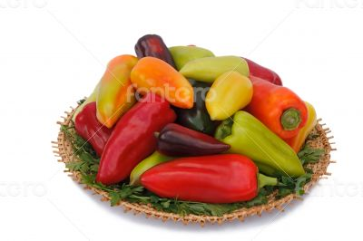 Red, yellow and green peppers on the wicker dish on a white back
