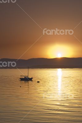 Sunset over the sea with sailing boat