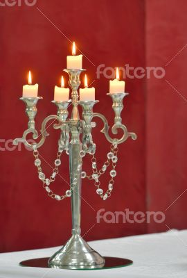 Silver classic candlestick isolated on red