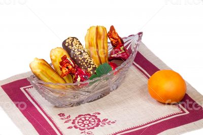 Cakes and sweets in a crystal vase, a tangerine, a napkin on a w