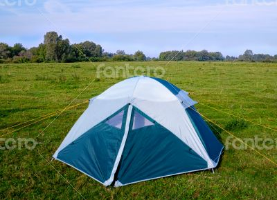 Private camping tent on the meadow near the river.