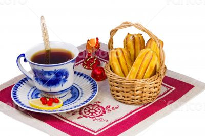 Cup of tea , candies and cakes in a wicker basket.