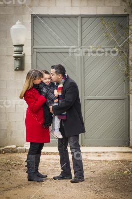 Warmly Dressed Family Loving Son in Front of Rustic Building