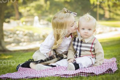 Sweet Little Girl Kisses Her Baby Brother at the Park