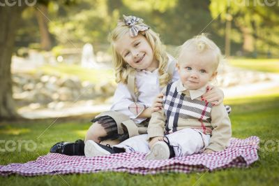 Sweet Little Girl Hugs Her Baby Brother at the Park