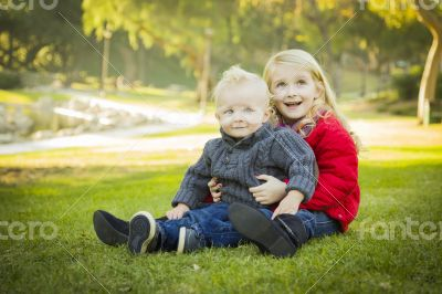 Little Girl with Baby Brother Wearing Coats at the Park