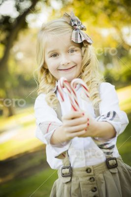 Cute Little Girl Holding Christmas Candy Canes Outdoors