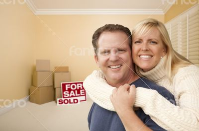 Couple in New House with Boxes and Sold Sale Sign
