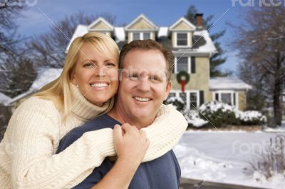 Couple in Front of Beautiful House with Snow on Ground