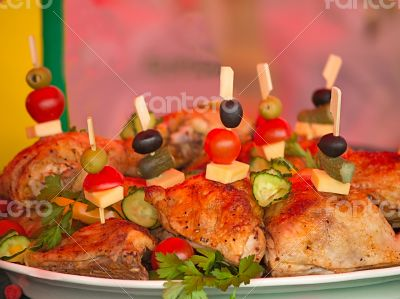 Fried chicken legs on a plate decorated with vegetables and herb